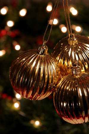 Three Golden Xmas Baubles hanging in front of a tree. photo
