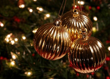 Three Golden Xmas Baubles hanging in front of a tree.