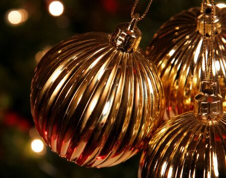 A closeup of a Golden Xmas Bauble hanging in front of a tree. photo