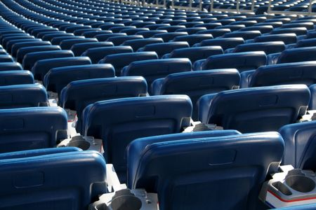 aisles: Red stadium seats cast in bright sunshine and shot from behind. Stock Photo