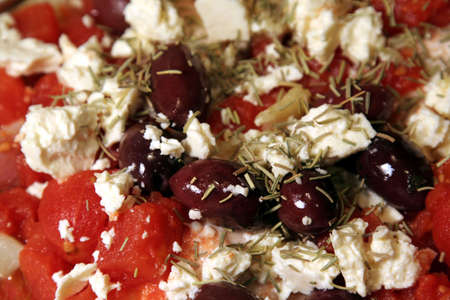 cloesup: A closeup of a Greek casserole featuring feta cheese, kalamata olives, tomatoes and rosemary.