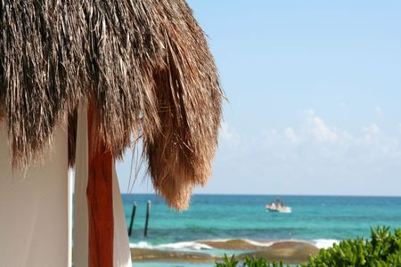 A palm hut with the beautiful Carribean sea in the background. Stock Photo - 2745536