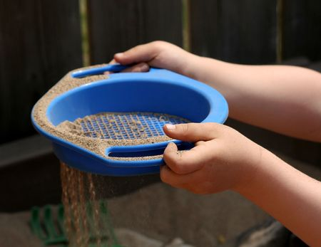 A childs hand sieving sand with a sieve.