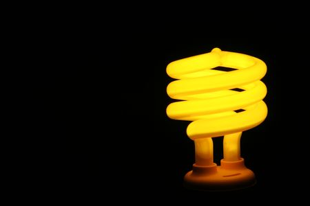 A yellow compact fluorescent energy saver light bulb set against a black background. Banco de Imagens