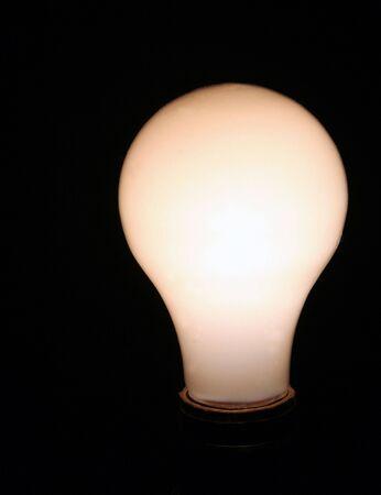 A incandescent light bulb set against a black background.