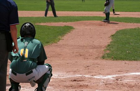 A shot from behind home plate, showing the catcher waiting for the pitch.