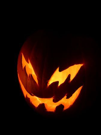 goblins: A spooky pumpkin face glowing on Halloween night.