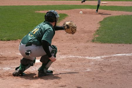 A catcher coming out his crouch to catch the pitch.