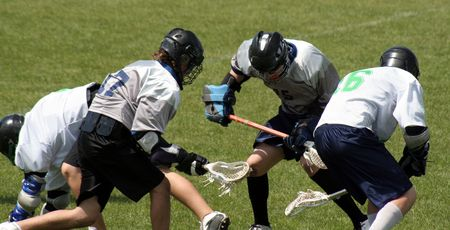 A lacrosse scrum featuring four players.