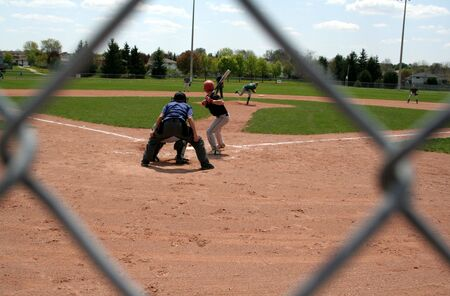 back link: A view through the chain link fence at a baseball game.