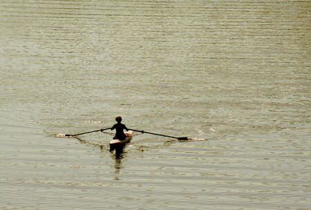 1 person: A kayakers silhouette as they skim across the river.