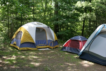 Three tents sitting in the shade on a campground.