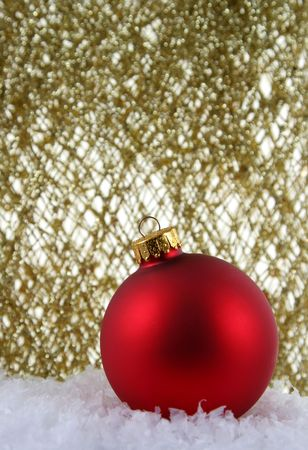 A red Christmas bauble backed by gold glittery strings. Stock Photo