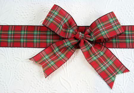装飾的な白い紙の上のクリスマスの格子縞弓。