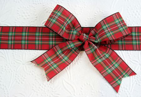 A plaid christmas bow on decorative white paper.