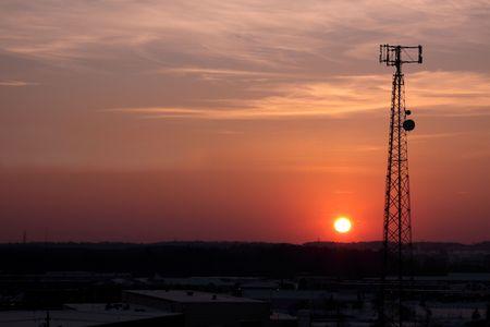 Het silhouet van een mobiele telefoon toren schot tegen de oranje cast van de ondergaande zon. Stockfoto