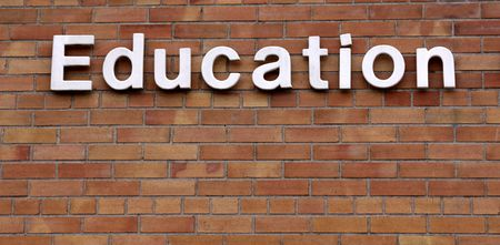 single word: The word education on a brick wall.