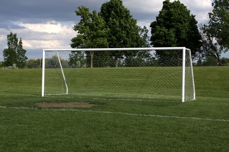 bounds: A view of a net on a vacant soccer pitch.
