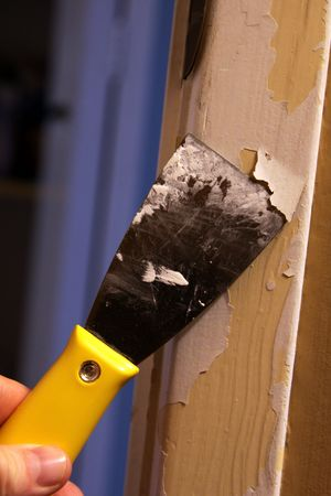 A close-up of a person stripping paint using a putty knife.
