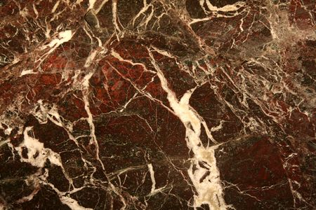 A red marble texture with white lines running through it. 写真素材