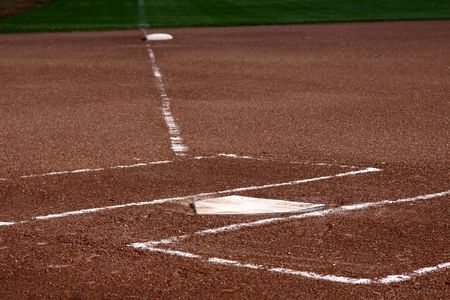 The view down the left field line with home plate and the batters boxes in focus.