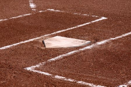 A close-up of the batters boxes and home plate on a vacant baseball diamond. photo