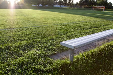 A brightly lit bench at a vacant soccer field. photo