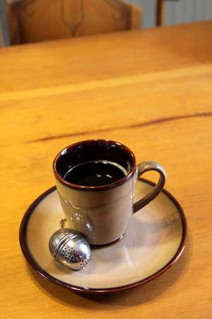 caffiene: A tea strainer sitting next to a mug of hot freshly brewed tea.