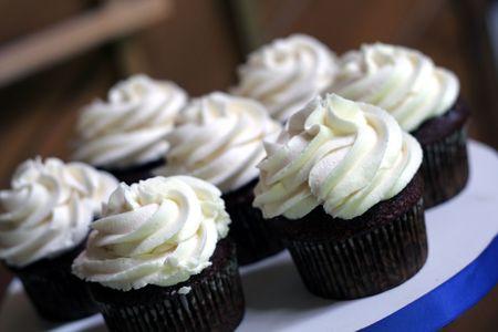 icing sugar: Yummy chocolate cupcakes with vanilla icing. Stock Photo