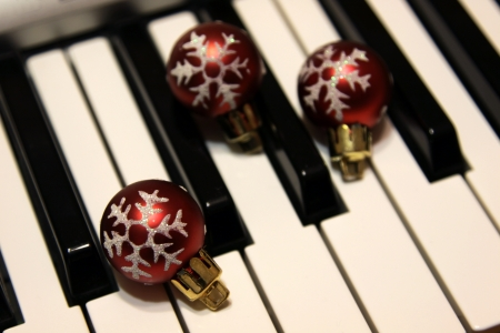 Three red snowflake Christmas baubles sitting on piano keys.  Stock Photo