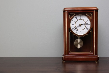 wood tick: A classic analog clock sitting a table with copy-space.