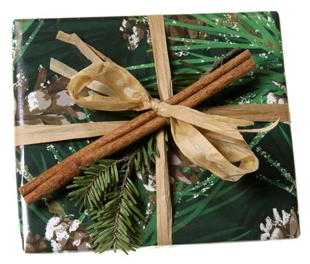 beautifully wrapped: A beautifully wrapped Christmas present, featuring green paper, cinnamon, and spruce branch.