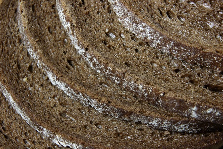 pumpernickel: A close-up of the crusts of five slices of pumpernickel bread.  Stock Photo