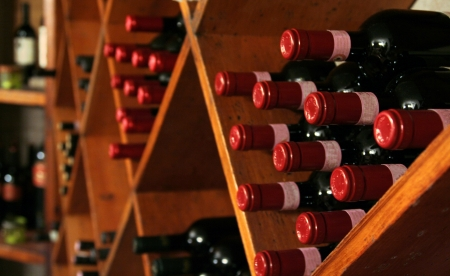 A buch of wine bottles in a rack in a wine cellar.