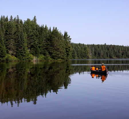 A father and two kids paddle in Pog Lake, in Algonquin Park, Ontario Canada. Stock Photo