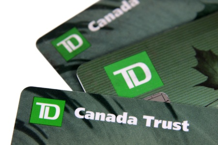 dominion: Toronto, Ontario, Canada - July 2, 2011: A closeup of three TD Canada Trust bank cards.  TD Canada Trust is one of the biggest banks in Canada.  They also operate internationally.