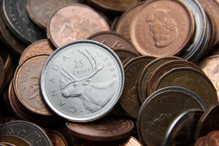 quarter: Toronto, Ontario, Canada, July 3rd, 2011: A Canadian Quarter with other coins in the background.  The Canadian currency is usually close in value to that of the US dollar. Editorial