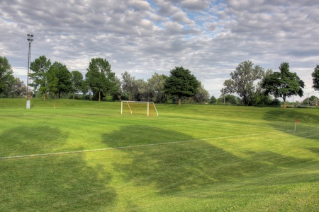 vacant: A cloudy unoccupied soccer field with trees in the background. (HDR photograph)