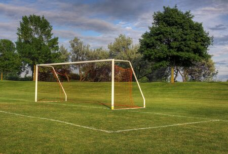 An empty soccer goal with trees in the background. (HDR photo)