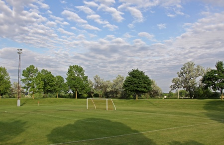 goalline: A mixed sky over an unoccupied soccer field with trees in the background.