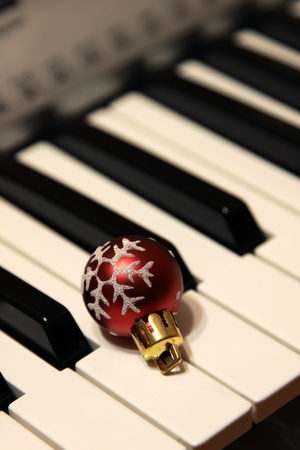 A red snowflake Christmas bauble sitting on piano keys.