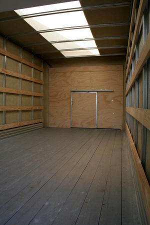 empty warehouse: The empty interior of the back of a moving truck. Stock Photo