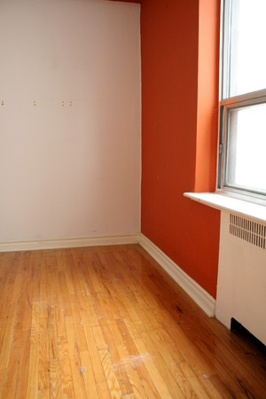hardwood: An empty orange and white room with a window and hardwood floors. Stock Photo