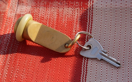 A large key from a hotel, sitting on a beach chair.