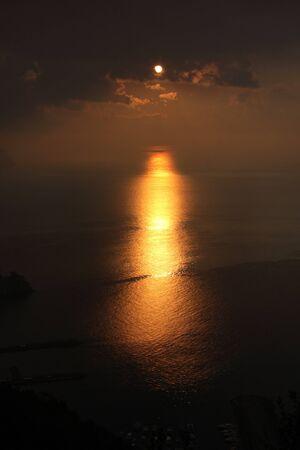イタリア、アマルフィの雲の切れ間から昇る太陽。