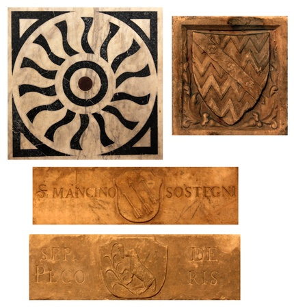 sheild: Four pieces of medieval stone work, featuring a marble sun design, a sheild relief and two name plates featuring shields.