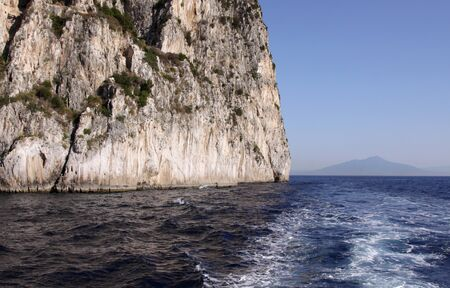 cliff face: A cliff face on the island of Capri and Mount Vesuvius in the background.  (Italy)