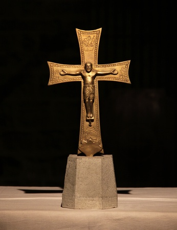 A gold sculpture of the Jesus Christ on the cross. (the crucifixion)  This is a medieval cross located in Florence, Italy. photo