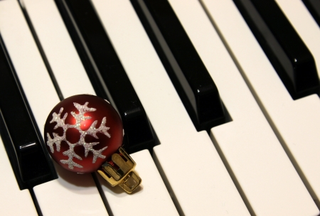 A red snowflake Christmas bauble sitting on piano keys. photo