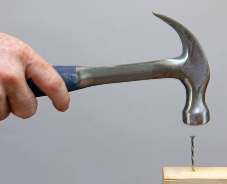 hammering: A person hammering a nail into a piece of wood. Stock Photo